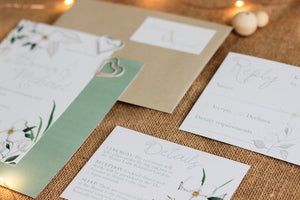 White and green floral invitation, information card and RSVP card laid out with a tag and envelope.