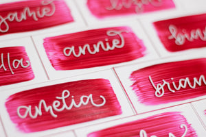 Acrylic place cards with hand-lettered names and rose-coloured painted backs.