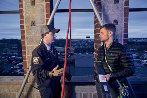 RopeSafe founder Jon Norton having a conversation with a firefighter about a rope chafe protection device.