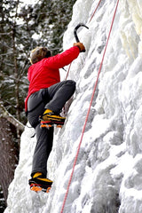 Man wearing a red jacket and gray pants climbing an ice wall with crampons
