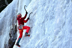 Woman in a colorful cold-weather outfit climbing a wall of ice with crampons