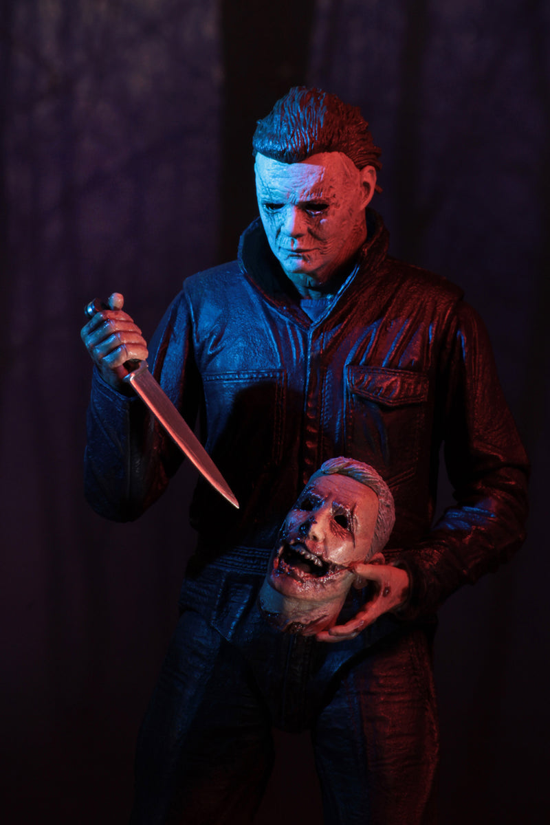 "This is a Halloween 2018 Michael Myers NECA 7"" ultimate action figure and he has a white mask, grey coveralls and black boots and he is holding a knife and a severed head."