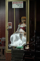 Annabelle NECA action figure from the Conjuring is sitting in a glass display case in a museum, on a rocking chair and has a white dress white a red sash and braids in her hair..