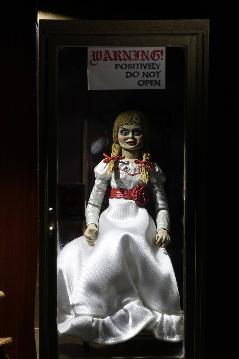 Annabelle NECA action figure from the Conjuring is sitting on a rocking chair in the Warren occult museum and has a white dress white a red sash and braids in her hair.