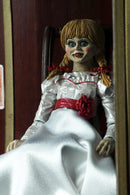 Annabelle NECA action figure from the Conjuring is sitting in a glass display case on a rocking chair and has 2 heads.