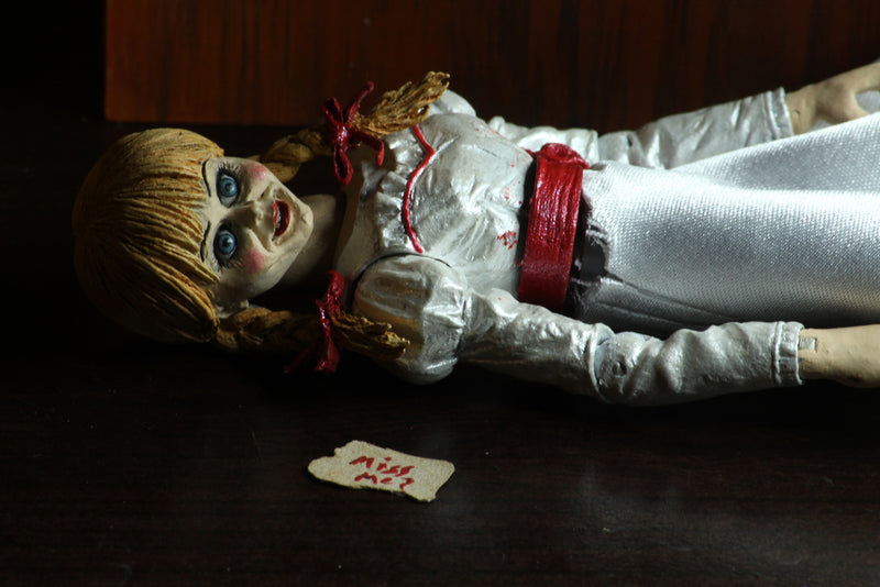 Annabelle NECA action figure from the Conjuring is laying down in a white dress with a red sash, next to a note she wrote in red letters that says miss me..
