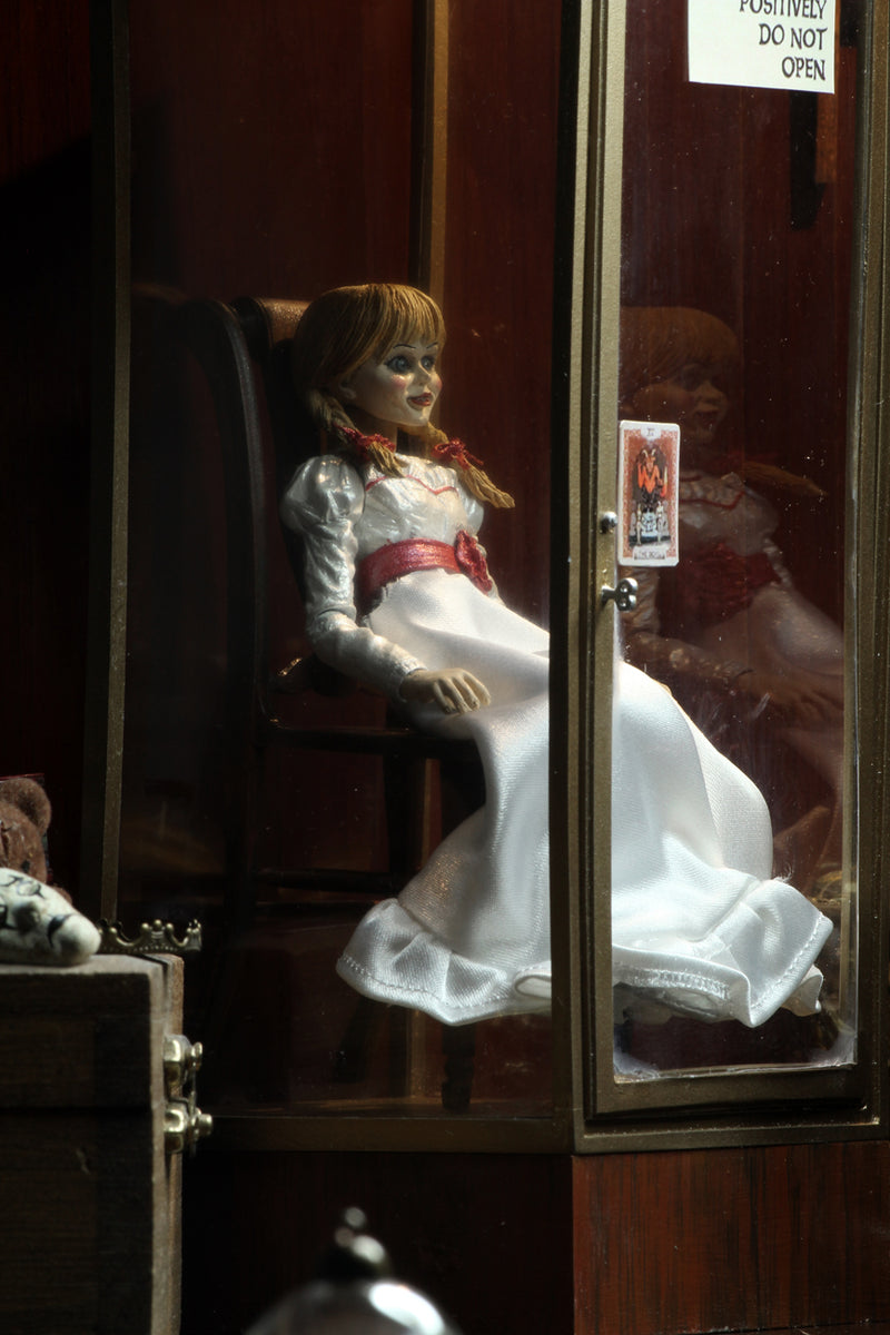 Annabelle NECA action figure from the Conjuring is sitting in a glass display case on a rocking chair and has a note that says miss me