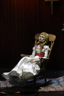 Annabelle NECA action figure from the Conjuring is sitting on a rocking chair and has a white dress white a red sash and braids in her hair..