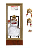 Annabelle from the Conjuring is sitting in a glass display case on a rocking chair and has 2 heads.