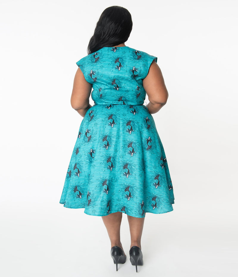 This is an aqua plus size vampire mermaid Unique Vintage dress that has  a belt and the model is wearing black shoes.