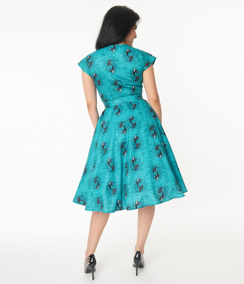 This is an aqua vampire mermaid Unique Vintage dress that has a belt and the model is wearing black and leopard shoes.