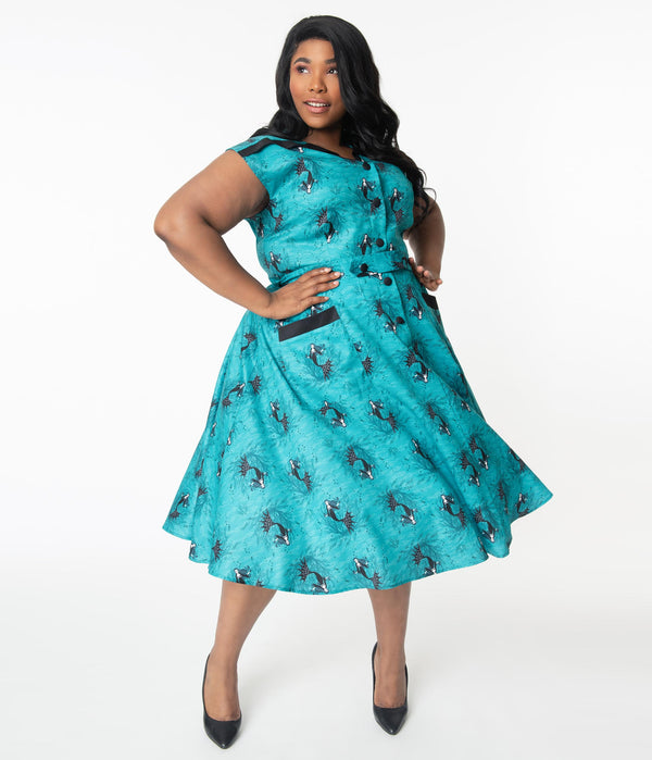 This is an aqua plus size vampire mermaid dress that has black buttons and pockets and the model is wearing black shoes.
