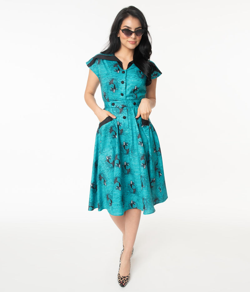 This is an aqua vampire mermaid dress that has black buttons and pockets and the model is wearing leopard shoes and sunglasses.