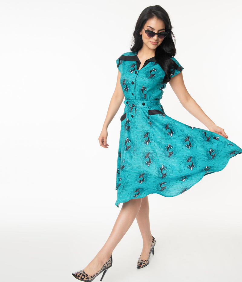 This is an aqua vampire mermaid Unique Vintage dress that has black buttons and pockets and the model is wearing leopard shoes and sunglasses.