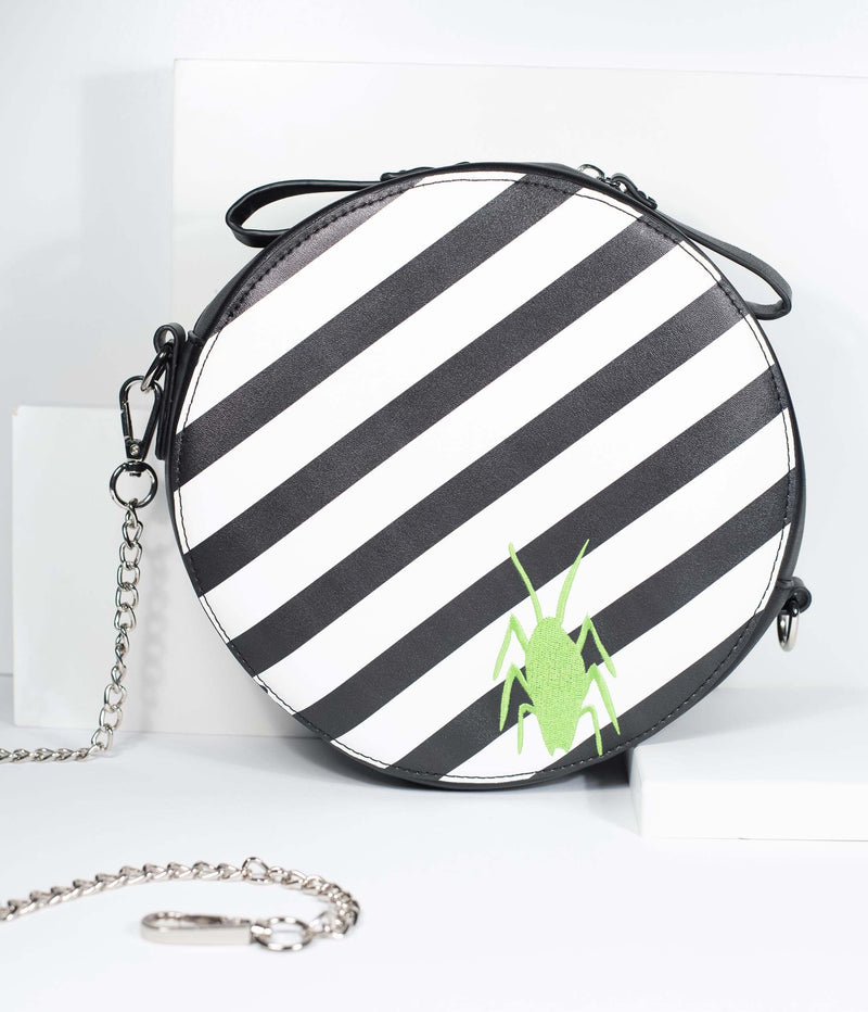 This is a Beetlejuice crossbody bag by Unique Vintage and it is black and white striped with a green bug on it.