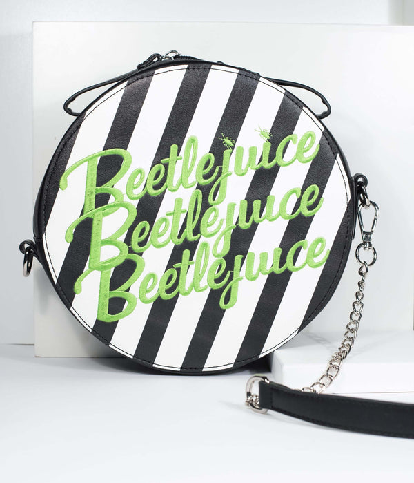 This is a Beetlejuice crossbody bag by Unique Vintage and it is black and white striped with Beetlejuice embroidered in green letters.