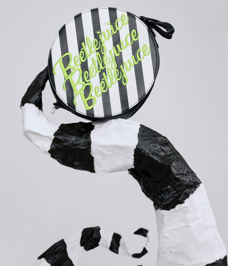 This is a Beetlejuice crossbody bag by Unique Vintage and it is black and white striped with Beetlejuice embroidered in green letters, with a black strap and it is on the sandworm..