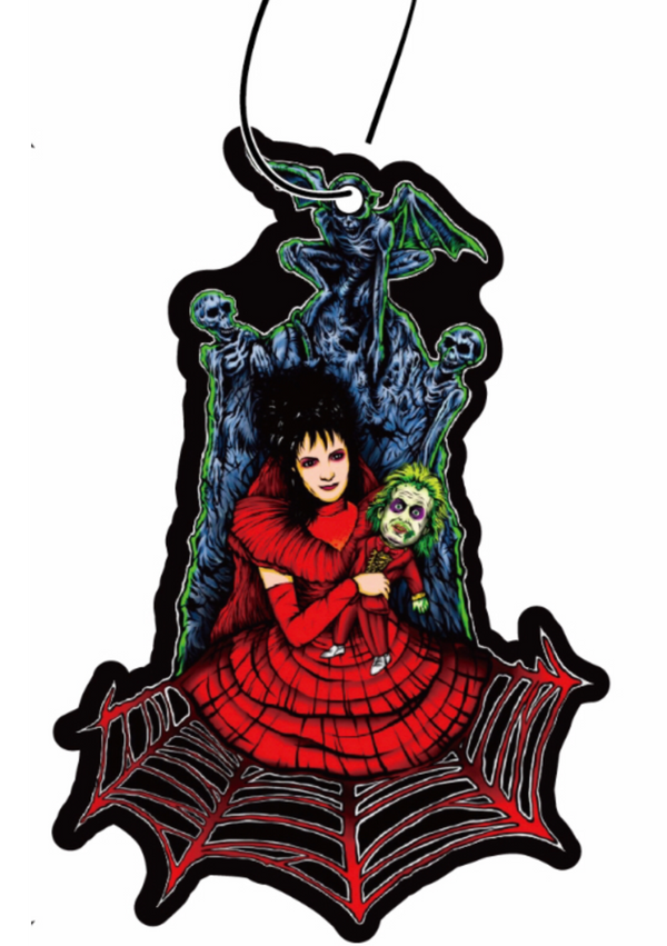 This is a Beetlejuice Lydia Deetz air freshener and she is wearing a red dress and holding a small Beetlejuice and is in front of a tombstone.