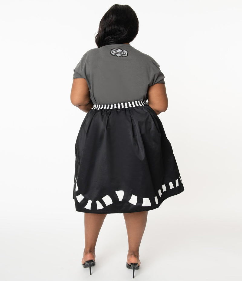 This is a Beetlejuice vintage pinup Sandworm swing skirt from Unique Vintage, that is black with a striped worm and the plus model is wearing a grey shirt and black shoes, with her hair to the side.