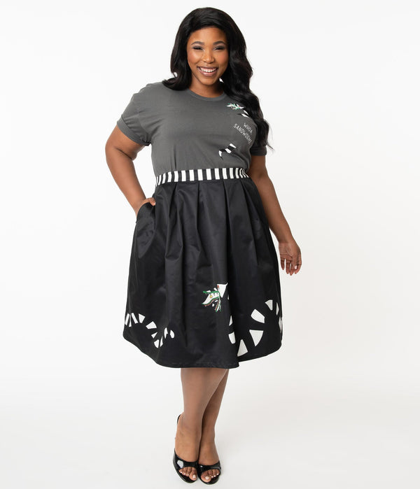 This is a Beetlejuice vintage pinup Sandworm swing skirt from Unique Vintage, that is black with a striped worm and the plus model is wearing a grey shirt and black shoes.