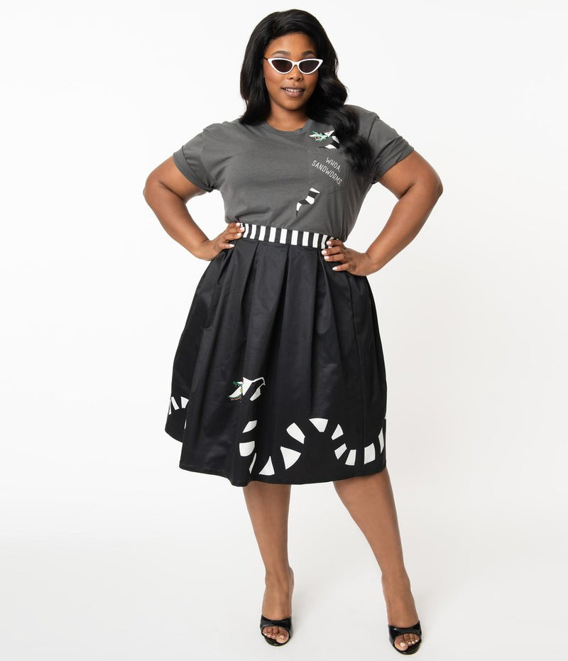This is a Beetlejuice vintage pinup Sandworm swing skirt from Unique Vintage, that is black with a striped worm and the plus model is wearing a grey shirt and black shoes and sunglasses.