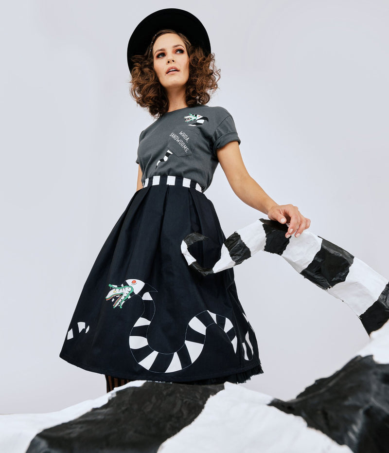 This is a Beetlejuice vintage pinup Sandworm swing skirt from Unique Vintage, that is black with a striped worm and the model is wearing a grey shirt and black hat.
