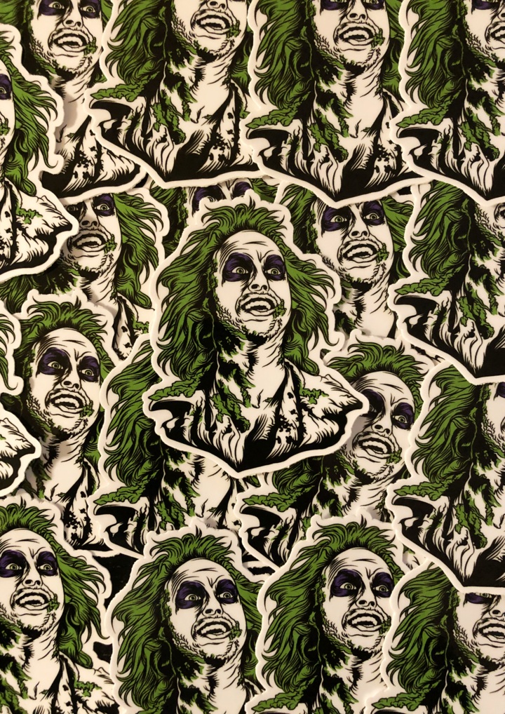 This is a collection of Beetlejuice head stickers and he has green hair, purple eyes and he has green on his face.