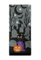 This is a grey hand towel and it has a black cat on a purple headstone in a cemetery, with an orange pumpkin, ghosts, bats crows, moons and glowing stars.