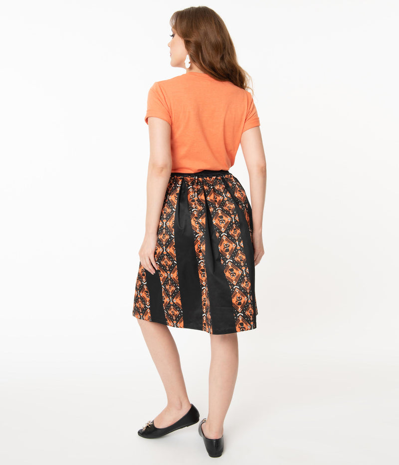 This is the back of a Unique Vintage Halloween swing skirt that has black cats, bats and skulls with orange print and the model is wearing an orange shirt.