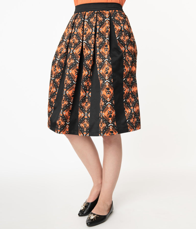 This is a Unique Vintage Halloween swing skirt that has black cats, bats and skulls with orange print and the model is wearing an orange shirt and black shoes with spiders.