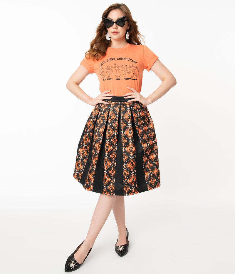 This is a Unique Vintage Halloween swing skirt that has black cats, bats and skulls with orange print and the model is wearing an orange shirt and sunglasses.