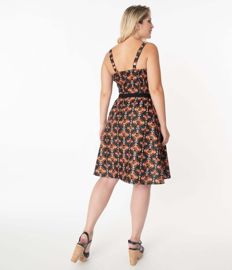 This is a Unique Vintage Halloween Rachel swing dress that has black cats, bats and skulls with orange print, 2 straps and the model is wearing black and cork shoes.