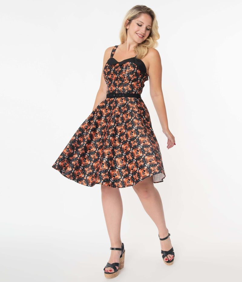 This is a Unique Vintage Halloween Rachel swing dress that has black cats, bats and skulls with orange print and the model is wearing black shoes.