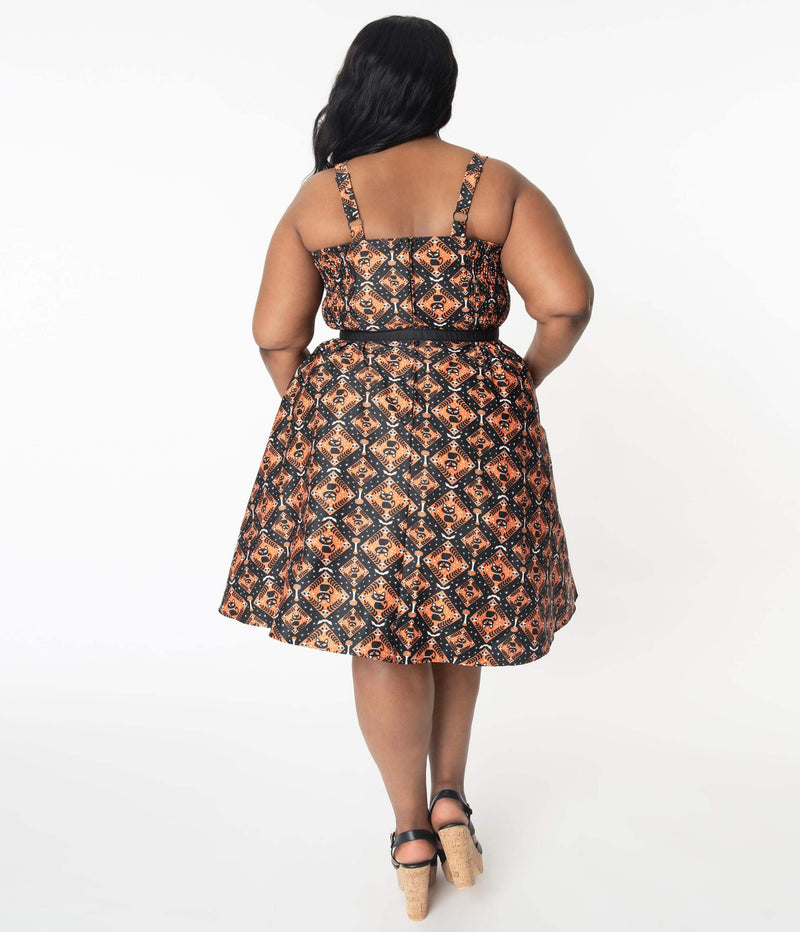 This is a Unique Vintage Halloween swing dress that has black cats, bats and skulls with orange print and the plus model is wearing black shoes and a belt.