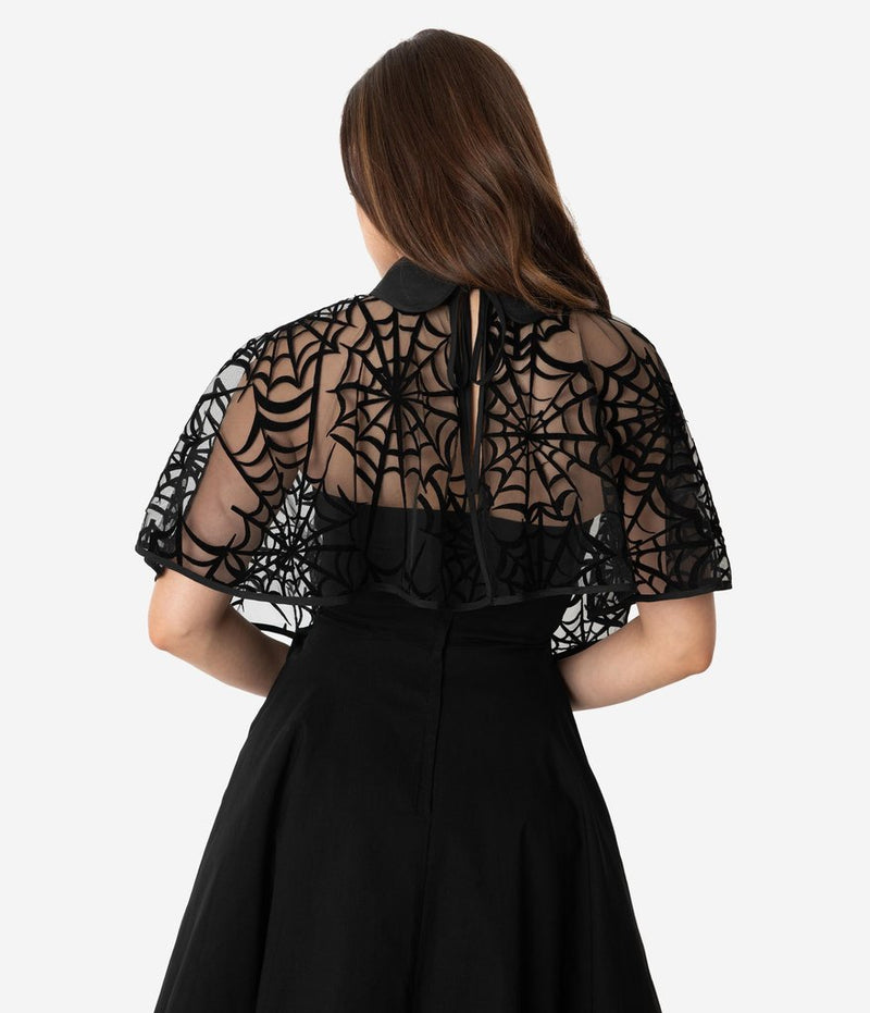 This is a black spiderweb cape, that is worn over the shoulders and the model has dark hair.