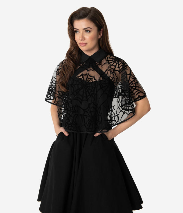 This is a black spiderweb cape, that is worn with a black dress with pockets and the model has dark hair.