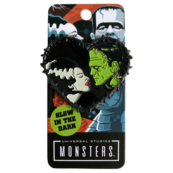 This is a Universal Monsters Bride of Frankenstein Heart enamel pin and has a woman with a white face, black hair that has a white streak and red lips and a greek man with black hair and stitches in his face.