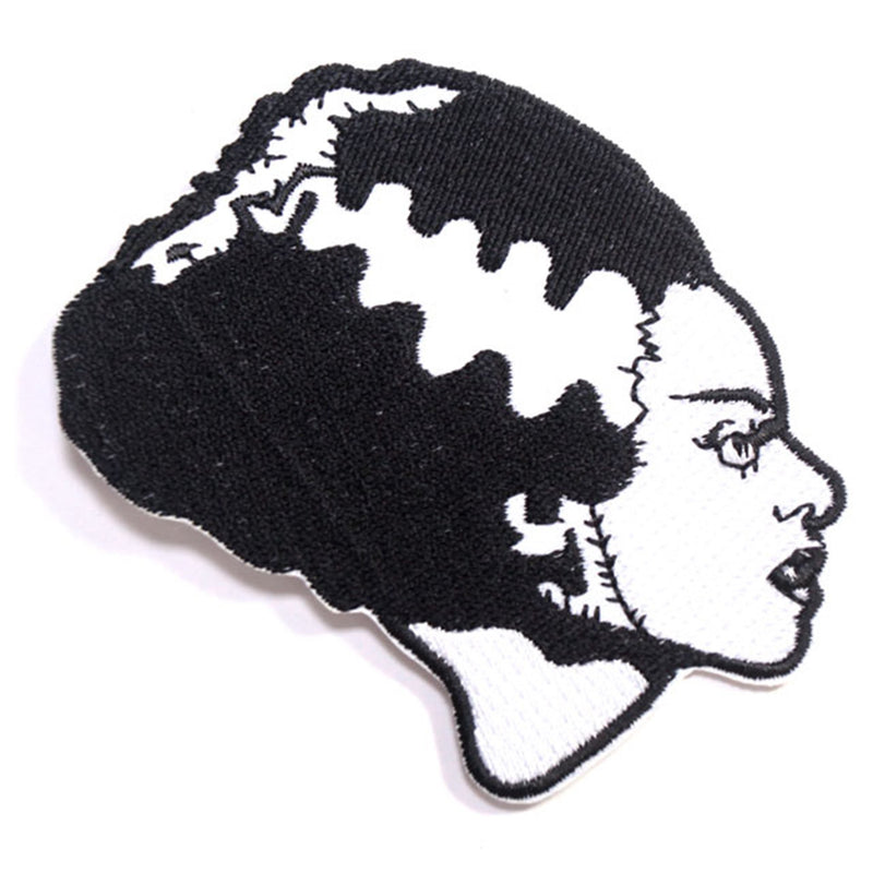 This is a Universal Monsters Bride of Frankenstein patch and she has black hair, with a white streak and stitch marks on her face.