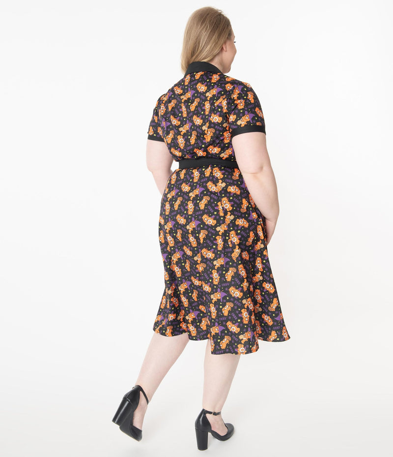 This is a Care Bears Halloween Creepy black swing dress from Unique Vintage and it has an orange trick-r-treat bear with a pumpkin, black belt, black collar and the plus model has blonde hair pulled to the side and is wearing black shoes.