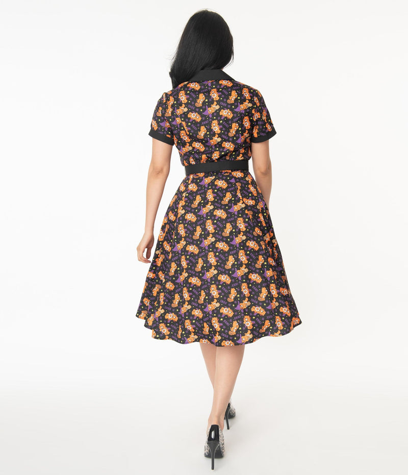 This is a Care Bears Halloween Creepy black swing dress from Unique Vintage and it has an orange bear with a pumpkin and the model has black hair pulled to the side and is wearing leopard print shoes.
