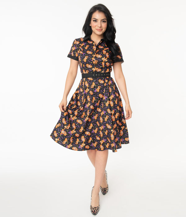 This is a Care Bears Halloween Creepy black swing dress from Unique Vintage and it has an orange bear with a pumpkin and the model has black hair and is wearing leopard print shoes.