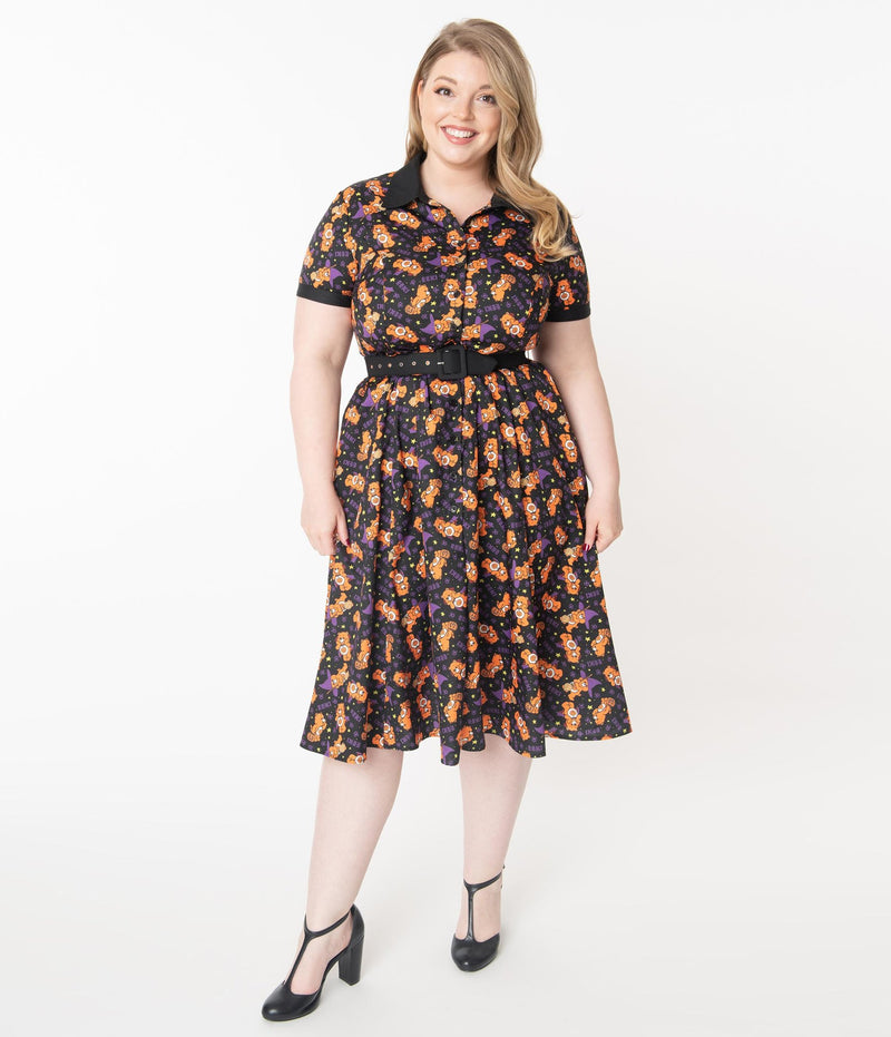 This is a Care Bears Halloween Creepy black swing dress from Unique Vintage and it has an orange trick-r-treat bear with a pumpkin, black belt, black collar and the plus model has blonde hair and is smiling and wearing black shoes.