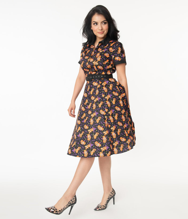 This is a Care Bears Halloween Creepy black swing dress from Unique Vintage and it has an orange trick-r-treat bear with a pumpkin, black belt, black collar and the model has black hair and is wearing leopard print shoes.