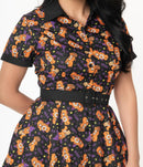 This is a Care Bears Halloween Creepy black swing dress from Unique Vintage and it has an orange bear with a pumpkin, purple witch hat and it has EEK! in the print and the model has dark hair.