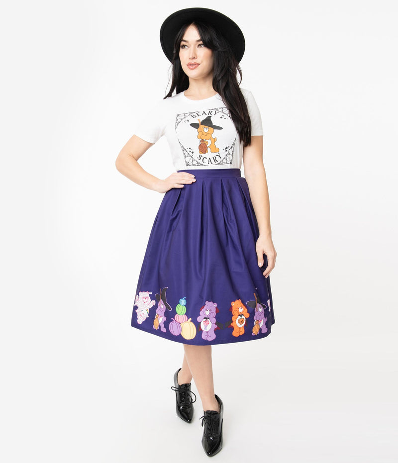 This is a Care Bears halloween purple Jayne swing skirt by Unique Vintage and the model is wearing a white shirt and has on black shoes and a black hat and her hand is on her hip.
