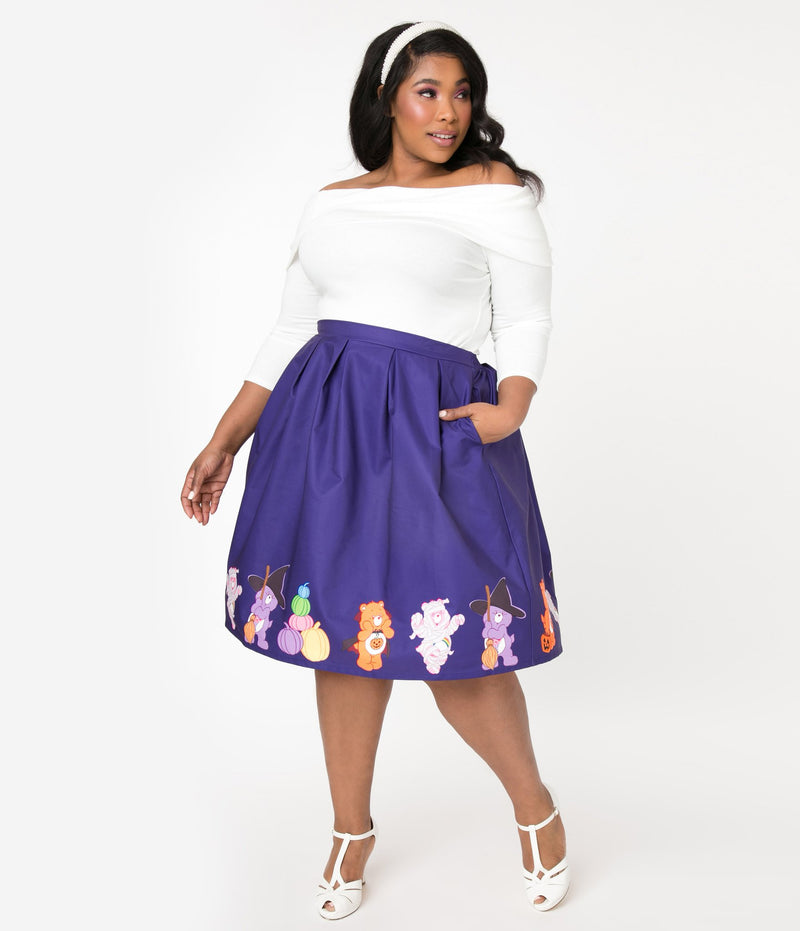 This is a Care Bears halloween purple Jayne swing skirt by Unique Vintage and the plus model is wearing a white shirt and has on white shoes and has her hand in her pocket.