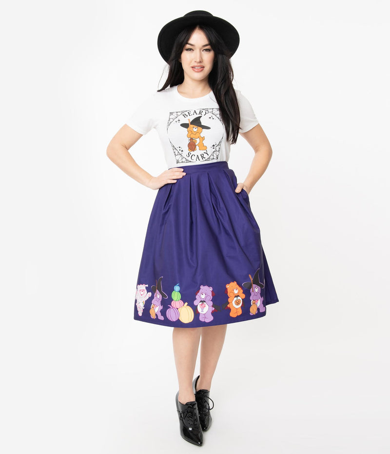 This is a Care Bears halloween purple Jayne swing skirt by Unique Vintage and the model is wearing a white shirt and has on black shoes and a black hat and her hands are on her hip and in her pocket.
