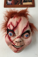 Chucky from Bride Of Chucky with orange hair and scars all over his face, hanging on a wall as house decor, under a photo..