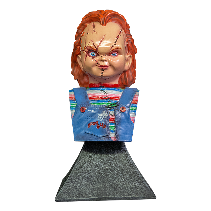 This is a Bride of Chucky mini bust and he has orange hair, a striped shirt, blue overalls and stitches on his face and is on a grey stand.