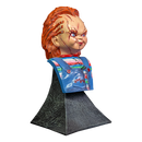 This is a Bride of Chucky mini bust and he has orange hair, a striped shirt, blue overalls and stitches on his face, has hair stapled to his head and is on a grey stand.